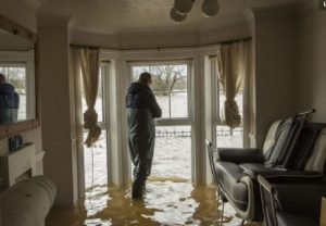 Homeowner assessing water damage in living room